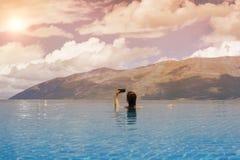 Jeune femelle dans la piscine sur le toit à l'arrière-plan de la ville grecque de Volos au coucher du soleil et aux montagnes Photo libre de droits