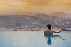Jeune femelle dans la piscine sur le toit à l'arrière-plan de la ville grecque de Volos au coucher du soleil et aux montagnes Images stock