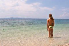 Jeune femelle dans le bikini faisant face à la mer, vue large Image stock