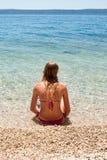 Jeune femelle dans le bikini se reposant en mer peu profonde, verticale Images libres de droits