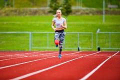 Jeune femelle dans les vêtements de sport fonctionnant sur des voies de sports Image stock