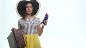 Jeune femelle dans occasionnel avec le sac de voyage, jugeant le passeport et les billets, d'isolement sur le fond blanc clips vidéos
