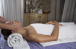 Jeune femelle décontractée obtenant un massage en pierre dans une station thermale Images libres de droits