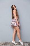 Jeune femelle de charme dans la robe d'été posant au-dessus du fond gris Photos stock