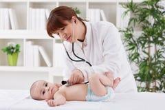 Jeune femelle de docteur examinant un patient de bébé images stock
