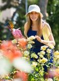 Jeune femelle de sourire dans l'uniforme au jardinage de yard Photo libre de droits