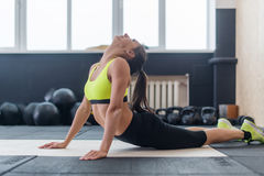 Jeune femelle faisant étirer de retour l'exercice, échauffement convenable de femme dans le gymnase Photo stock