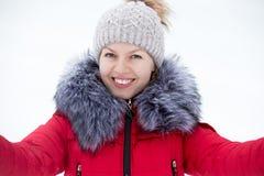 Jeune femelle heureuse dans la veste rouge d'hiver prenant l'autoportrait, OU Images libres de droits