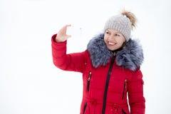 Jeune femelle heureuse dans la veste rouge d'hiver prenant la photo avec smar Photos stock