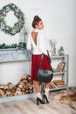 Jeune femelle magnifique dans une jupe rouge et position blanche de pull dans une salle décorée par Noël Jambes érotiques dans le photographie stock libre de droits