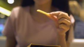 Jeune femelle prenant les pommes frites croustillantes, casse-croûte malsain dans le restaurant d'aliments de préparation rapide banque de vidéos
