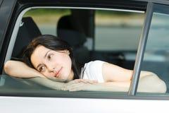 Jeune femelle regardant à l'extérieur l'hublot de véhicule Photographie stock