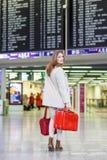 Jeune femme à l'aéroport international, vérifiant le conseil électronique Photographie stock libre de droits