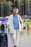 Jeune femme à l'aéroport international, vérifiant le conseil électronique Images stock