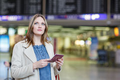 Jeune femme à l'aéroport international, vérifiant le conseil électronique Image libre de droits