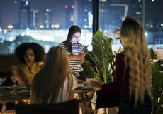 Jeune femme à l'aide d'un smartphone la nuit dîner n'ayant pas inter Image stock