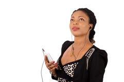 Jeune femme à l'aide d'un téléphone portable avec des écouteurs Photographie stock libre de droits