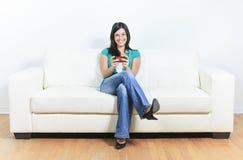 Jeune femme à l'aide d'un téléphone portable sur le sofa photos stock