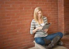 Jeune femme à l'aide de l'ordinateur de comprimé Photos libres de droits
