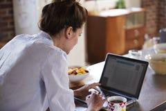 Jeune femme à l'aide de l'ordinateur portable au petit déjeuner, au-dessus de la vue d'épaule image stock