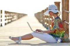 Jeune femme à l'aide de l'ordinateur portable extérieur en été Photographie stock