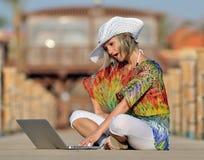 Jeune femme à l'aide de l'ordinateur portable extérieur en été Images stock