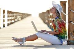 Jeune femme à l'aide de l'ordinateur portable extérieur en été Photo libre de droits