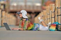 Jeune femme à l'aide de l'ordinateur portable extérieur en été Photographie stock libre de droits