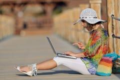 Jeune femme à l'aide de l'ordinateur portable extérieur en été Image stock