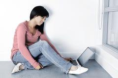Jeune femme à l'aide de l'ordinateur portable sur l'étage photographie stock libre de droits