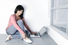 Jeune femme à l'aide de l'ordinateur portable sur l'étage Photos stock