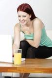 Jeune femme à l'aide de l'ordinateur portatif à la maison Photos libres de droits