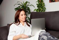 jeune femme à l'aide de l'ordinateur portatif à la maison Images libres de droits