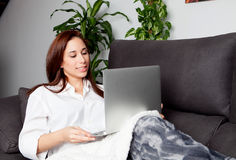 jeune femme à l'aide de l'ordinateur portatif à la maison Photos stock
