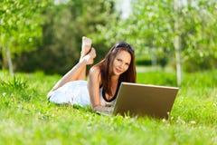 Jeune femme à l'aide de l'ordinateur portatif dans le stationnement Photo libre de droits