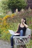 Jeune femme à l'aide de l'ordinateur portatif et du portable dans le stationnement Photo stock