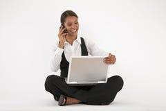 Jeune femme à l'aide de l'ordinateur portatif et du téléphone portable Image libre de droits