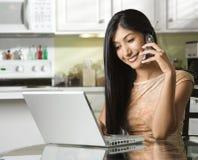 Jeune femme à l'aide de l'ordinateur portatif et parlant sur le portable Photographie stock libre de droits