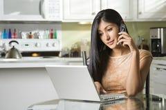 Jeune femme à l'aide de l'ordinateur portatif et parlant sur le portable Images libres de droits