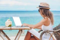 Jeune femme à l'aide de l'ordinateur portatif sur la plage Travaillent en indépendants le travail Images stock