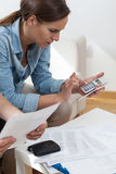 Jeune femme à l'aide de la calculatrice Image stock