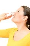 Jeune femme à l'aide de la pulvérisation nasale Photographie stock libre de droits