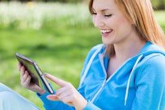 Jeune femme à l'aide de la tablette digitale à l'extérieur Photographie stock