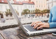 Jeune femme à l'aide de l'ordinateur portable au café dehors Jeune belle fille travaillant sur l'ordinateur dans une ville photos stock