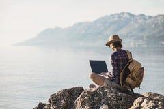 Jeune femme à l'aide de l'ordinateur portable sur une mer Travaillent en indépendants le concept de travail photos stock