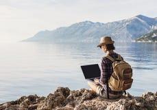 Jeune femme à l'aide de l'ordinateur portable sur une mer Travaillent en indépendants le concept de travail images libres de droits
