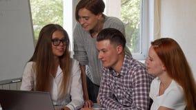 Jeune femme à l'aide de l'ordinateur portable, travaillant sur un projet avec ses camarades de classe banque de vidéos
