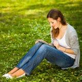 Jeune femme à l'aide de sa tablette tout en détendant dehors Image libre de droits
