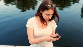 Jeune femme à l'aide de sa tablette tout en détendant dehors dans un parc une belle journée de printemps près de la rivière clips vidéos
