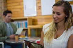 Jeune femme à l'aide du comprimé en café images stock